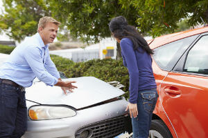 man and woman arguing after car crash