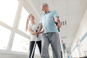 physical therapist helping patient with walking