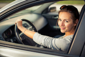 woman driving car with one hand